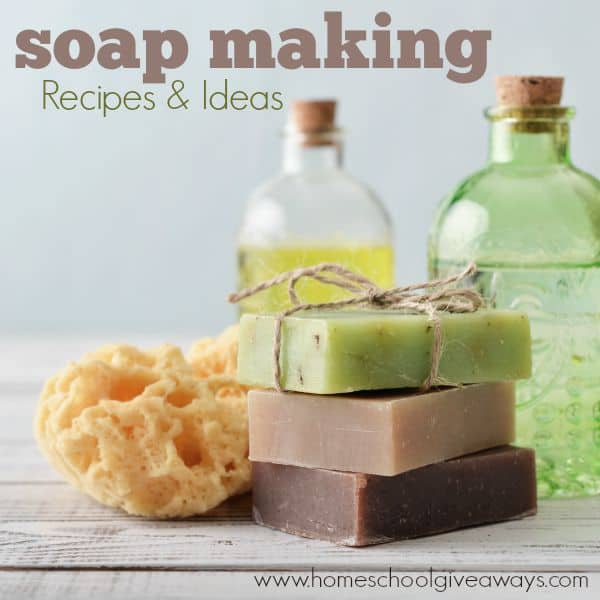 Stack of soap bars with sponge and bottles on light background