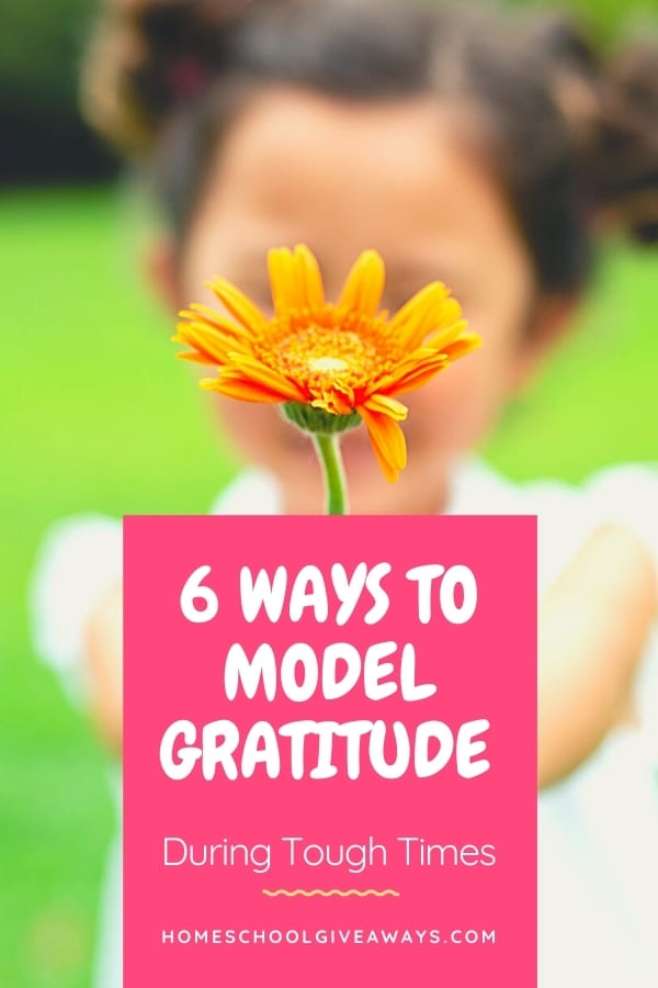 image of child holding orange flower with text ovelay. 6 ways to model gratitude during tough times. www.HomeschoolGivaways.com